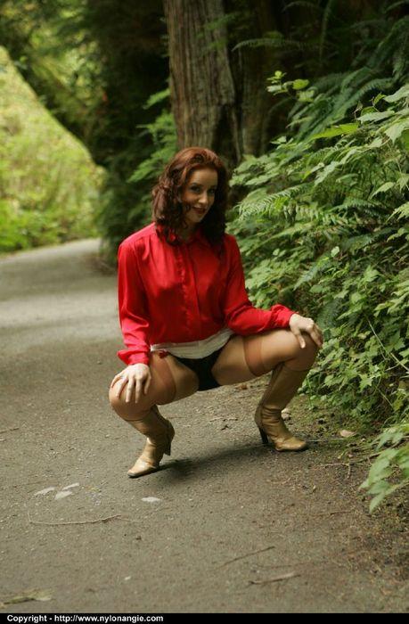 Рыжая зрелка в сапогах и чулках задирает белую юбку в парке